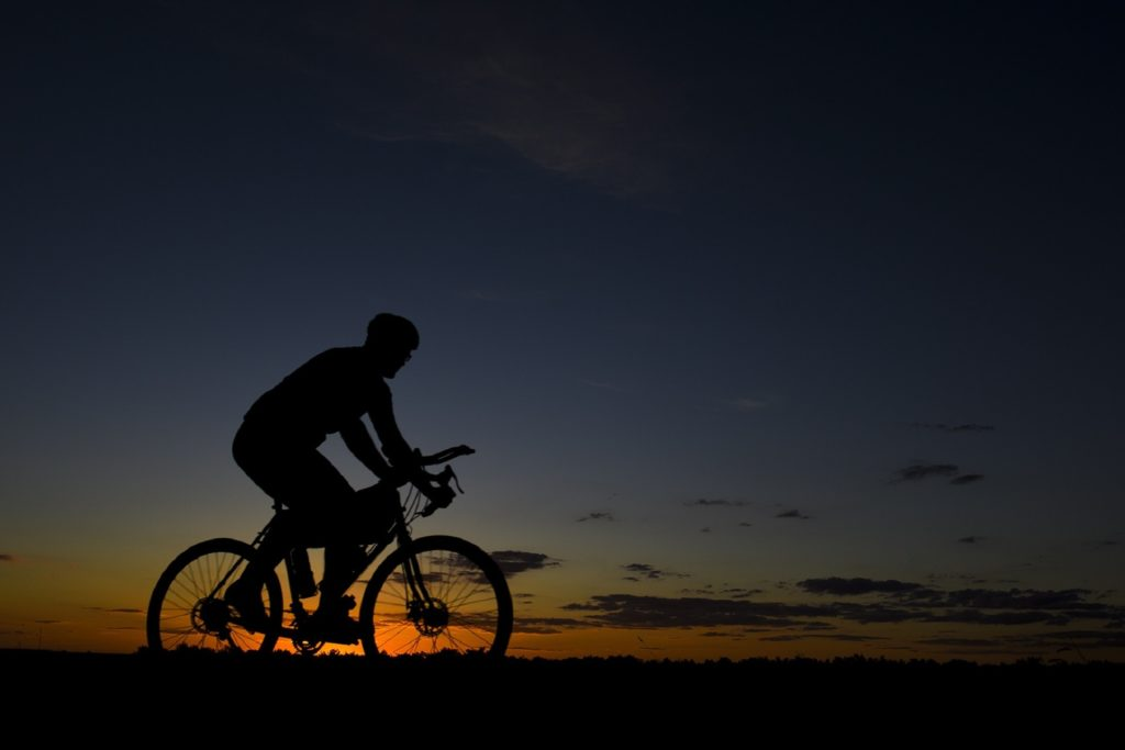 Man on bike next to sunset